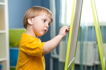 Child boy draws on chalkboard