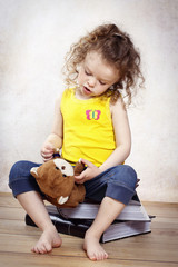 Little girl playing with teddie bear