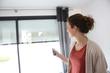 Leinwanddruck Bild - Woman using remote control to open electric shutter
