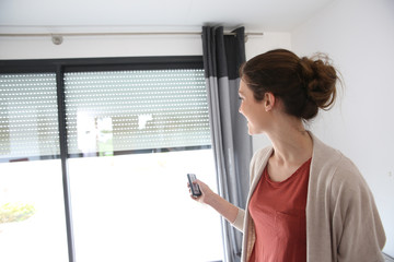 Woman using remote control to open electric shutter