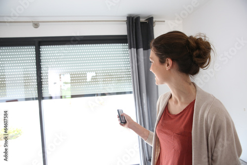 Woman using remote control to open electric shutter - 64607584