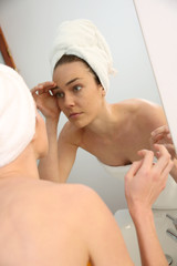 Woman in bathroom looking in mirror