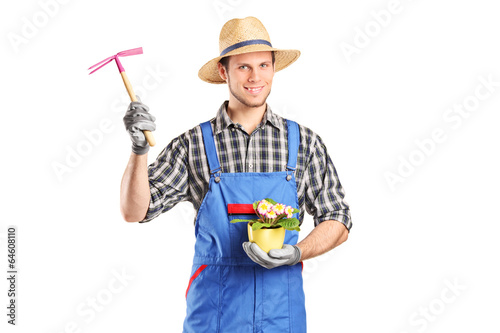 Male gardener holding flower plant and a mattock