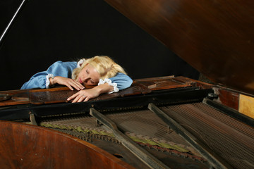 Baroque woman sleeping onon an old grand piano