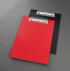 Red and black plastic clipboard on gray background.