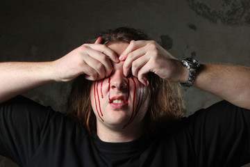 Man taking out his eyes, full of blood