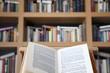 Libro abierto sobre atril con fondo de librería