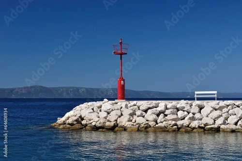 Red lighthouse with stones and white bench. Podgora, Croatia - 64608934