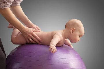 Woman is doing massage her baby