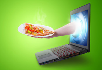 Hand holding a pizza slice coming out of a laptop screen