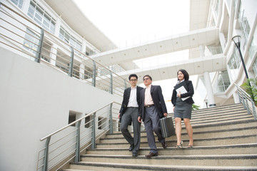 asian business team walking out of office area