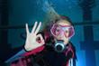 Female scuba diver show underwater signal - 64613176