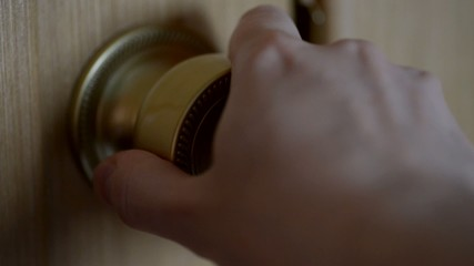 Hand trying to unlock door knob.