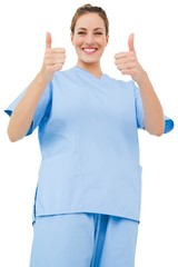 Pretty surgeon in blue scrubs giving thumbs up