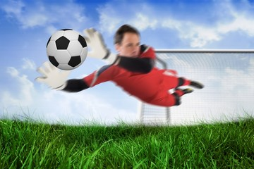 Fit goal keeper jumping up and saving ball