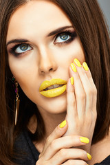 Make up. Beautiful model portrait with yellow lips and nails.