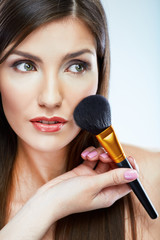 Beautiful woman face. Make up applying with brush.