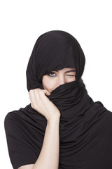 Transgressive girl wearing a burqa and uncovering