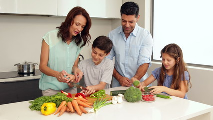 Mother showing her children how to chop vegetables