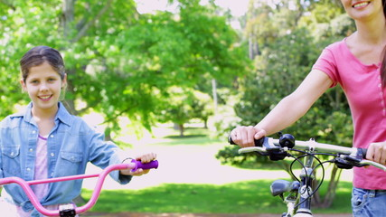 Cute mother and daughter pushing their bikes together in the par