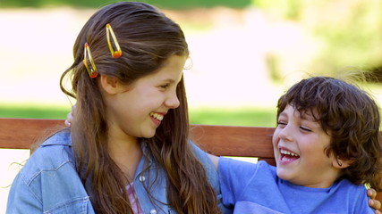Brother and sister laughing together on park bench