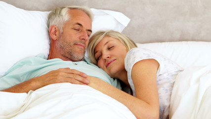 Couple lying in bed and cuddling
