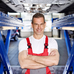 Master mechanic under a service lift in a garage