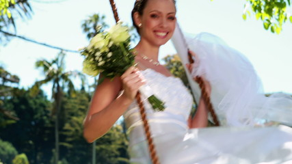 Pretty bride sitting on a swing smiling at camera