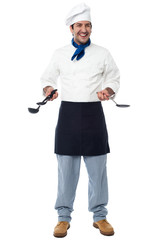Smiling chef with kitchen utensils
