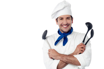 Smiling chef holding kitchenware