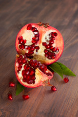 Fresh ripe pomegranate with leaves on a wooden board.