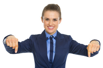 Smiling business woman pointing down on copy space