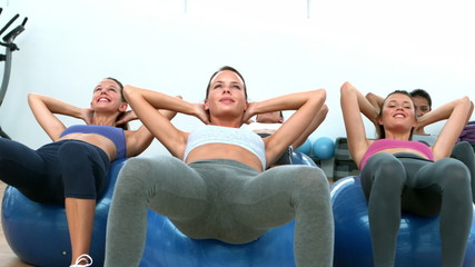 Fitness class doing sit ups on exercise balls