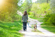 Young woman with her dog walking on the village back to camera
