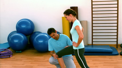 Woman doing lunges with her trainer