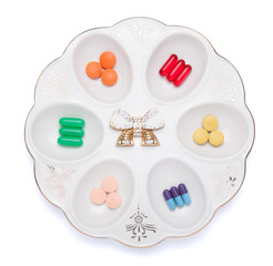 Pills, capsules and tablets on white plate