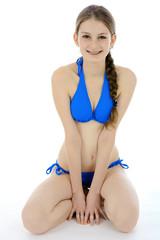 Teenager im Bikini kniet