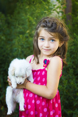 Charming girl holding a puppy