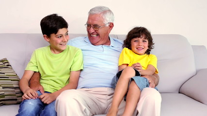 Senior man sitting on couch with his grandsons