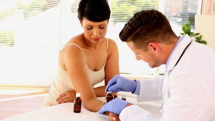 Dermatologist applying ointment to womans arm