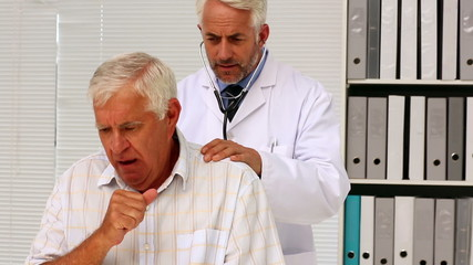Doctor examining his senior patient who has a cough