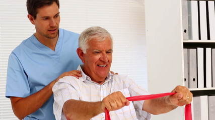 Male nurse showing elderly patient how to use resistance band