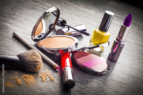 Cosmetics on black slate background