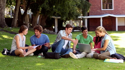 Classmates sitting on the grass chatting