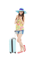 happy woman looking the smart phone with  travel baggage