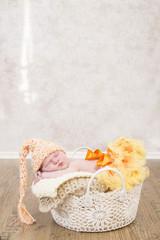 Newborn Baby in einem Häkelkorb, schlafend mit süßer Mütze