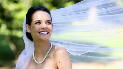 Beautiful bride smiling at camera in the park