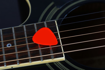 Colourful plectrum on guitar, close up