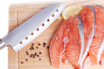 Red salmon on board with knife above