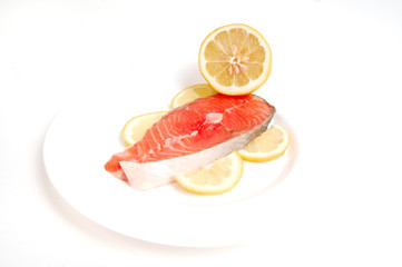 Salmon steak on plate with lemon